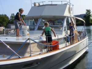 Second Place in 2017 Nautical Delights photo contest depicts three youngsters cleaning a 1967 Chris Craft Commander.