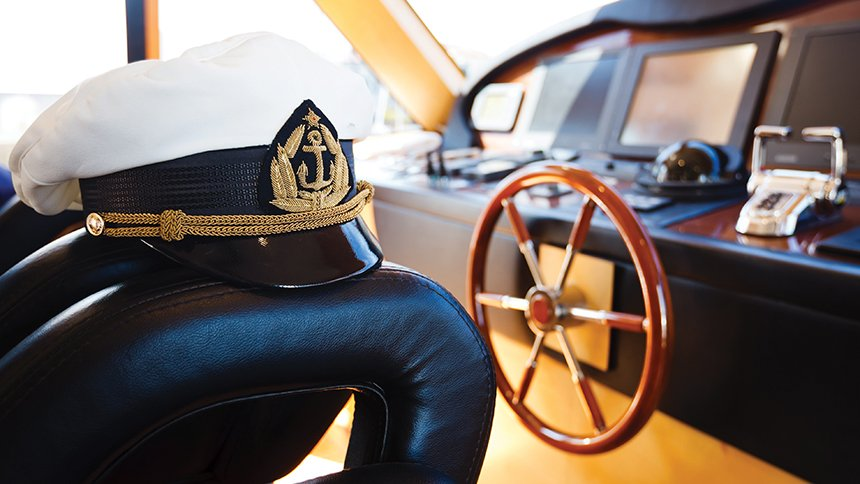 A picture of a captain's hat and a steering wheel on a boat