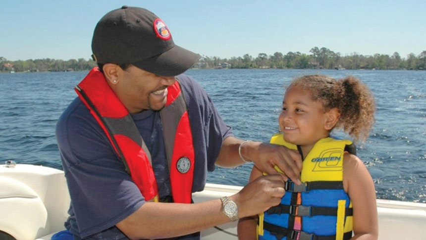 Photo of father helping daughter secure her life jacket.