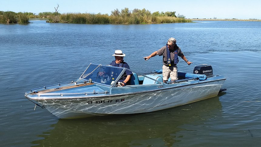 Gary Rogers steers his boat as Doug Sherman instructs.