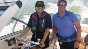 Photo of youth piloting a boat during Day on the Water